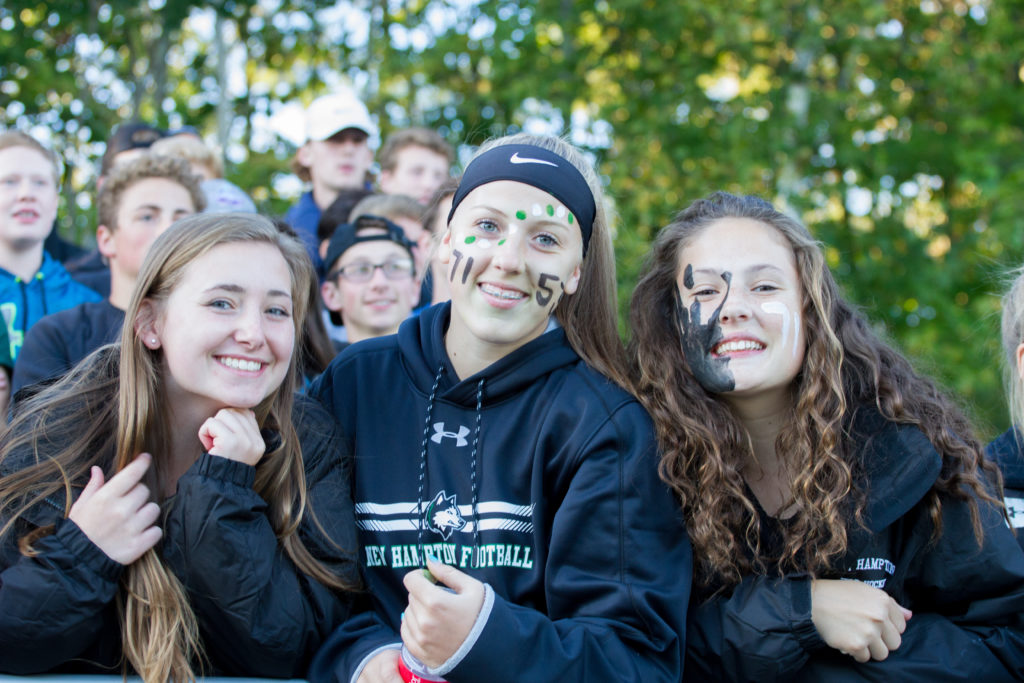 New Hampton School students cheer on their peers at a football game.