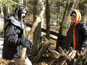Students learn to build debris shelters in the woods near campus.