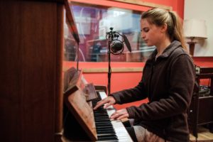 student singing and playing piano in the recording studio.