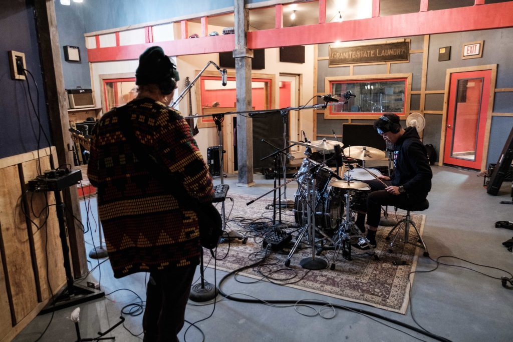 Students recording bass, drums, and vocals in the studio.