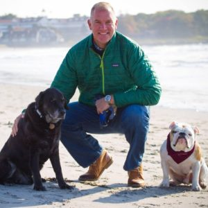 Head of School Joe Williams wearing jeans and thin green puffy jacket with his black lab and english bulldog on the beach