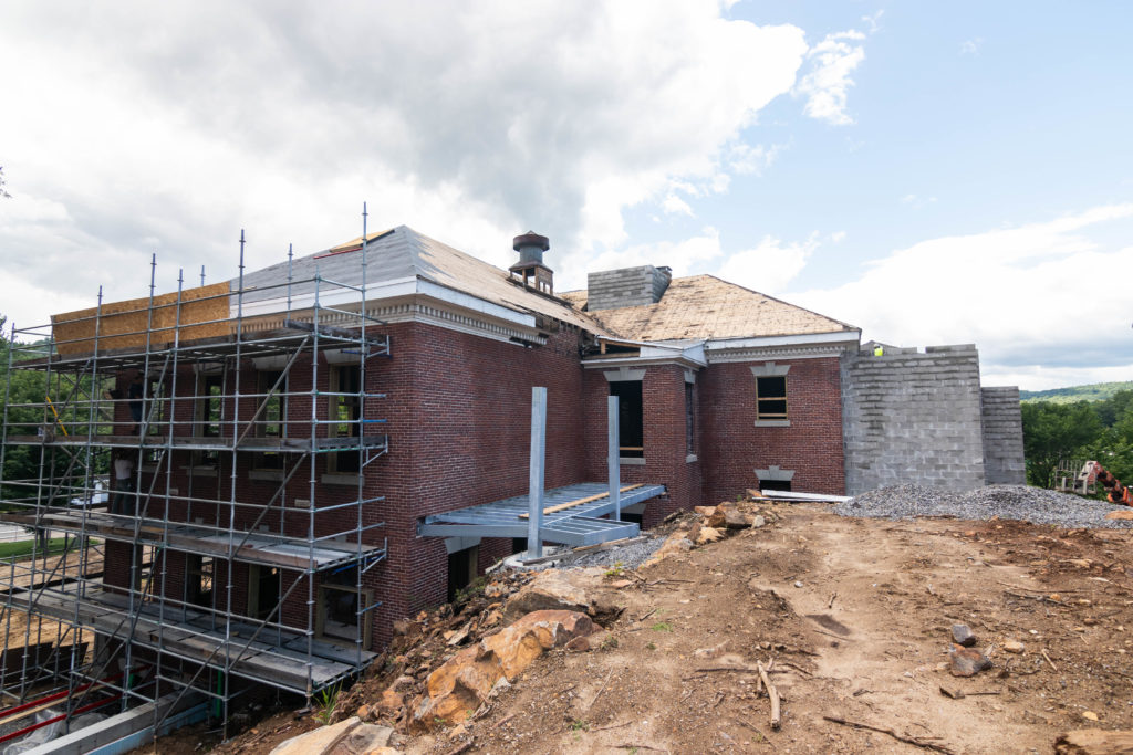 Brick building under construction with metal scaffolding and concrete addition; Lane Hall looks to the future for completion