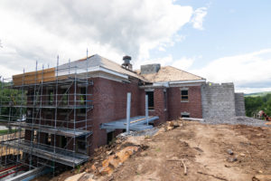 Brick building under construction with metal scaffolding and concrete addition