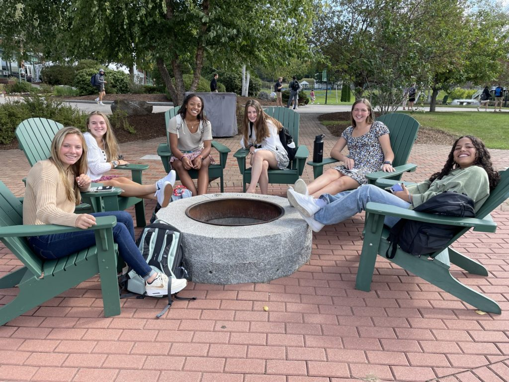 Group of high school girls sitting in green adirondack chairs on a red brick patio around a firepit