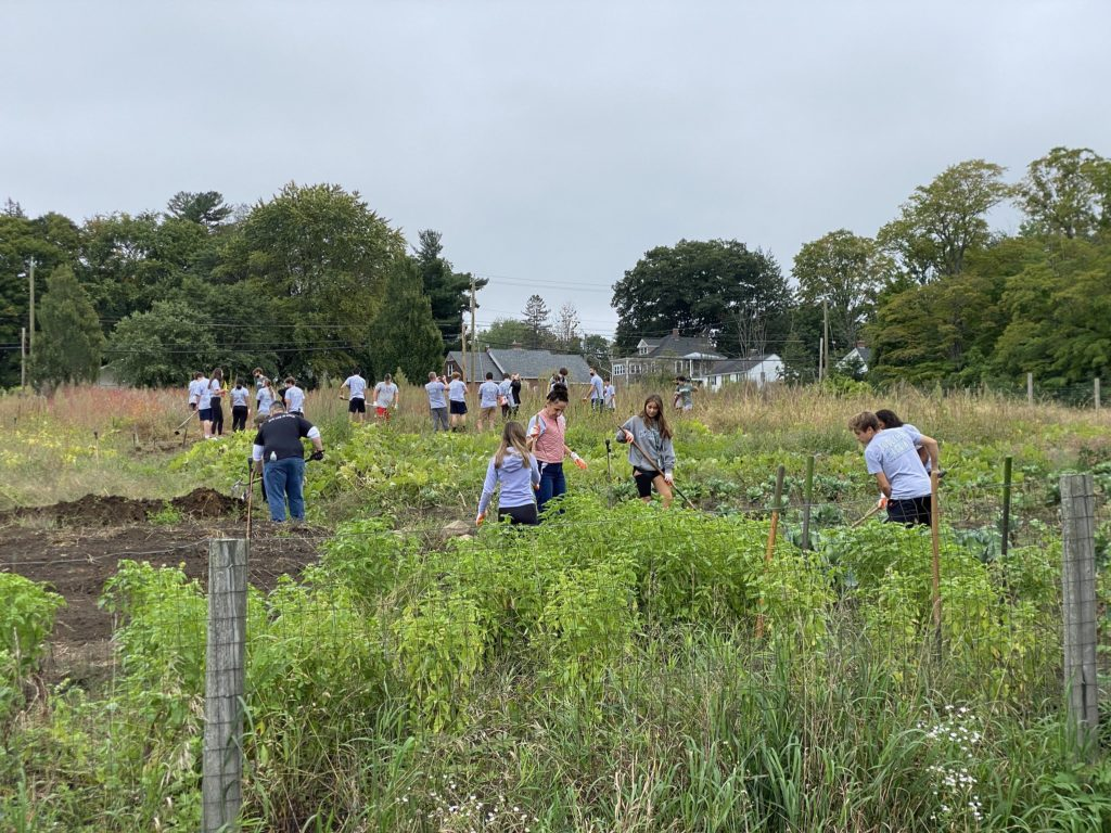 Group of high school students working with yard equipment in a green field